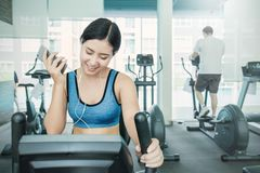 Attractive young asian woman working out with exercise machine at the gym royalty free stock photography