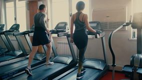 Beautiful sporty brunette Woman of average years walking, running on treadmill gym workout. 4 k. Beautiful sporty brunette middle aged Woman walking, running on stock footage