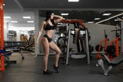 A beautiful sporty brunette is standing in the gym Royalty Free Stock Image