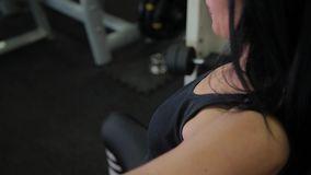 Beautiful sporty brunette woman is engaged on a simulator for the muscles of the chest and arms. Lifestyle concept. stock video
