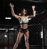 Beautiful sporty brunette woman in a gym behind an iron grid Royalty Free Stock Images