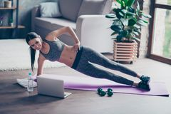 Beautiful sporty cheerful woman is doing side plank exercise. Sh royalty free stock image