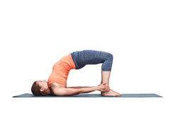 Beautiful sporty fit yogi girl practices yoga asana setu bandhas. Beautiful sporty fit yogini woman practices yoga asana setu bandhasana - bridge pose advanced royalty free stock image