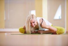 Beautiful sporty fit yogi woman practices yoga asana Adho Mukha Baddha Konasana - butterfly pose in the fitness room. Beautiful sporty fit yogi woman practices Royalty Free Stock Photo