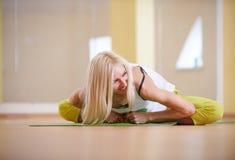 Beautiful sporty fit yogi woman practices yoga asana Adho Mukha Baddha Konasana - butterfly pose in the fitness room. Beautiful sporty fit yogi woman practices Stock Photography