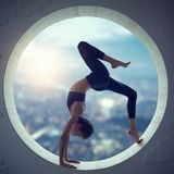 Beautiful sporty fit yogi woman practices yoga asana Eka Pada Urdhva Dhanurasana in a round window. With a view of the city at sunset stock photo