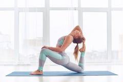 Beautiful sporty fit yogi woman practices yoga asana King Pigeon pose rajakapotasana at the yoga studio Stock Photography