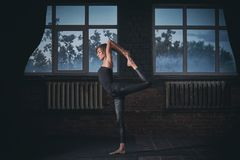 Beautiful sporty fit yogi woman practices yoga asana Natarajasana - Lord Of The Dance pose in the dark hall Stock Images