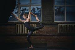 Beautiful sporty fit yogi woman practices yoga asana Natarajasana - Lord Of The Dance pose in the dark hall Stock Image