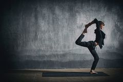 Beautiful sporty fit yogi woman practices yoga asana Natarajasana - Lord Of The Dance pose in the dark hall.  royalty free stock photo