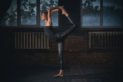 Beautiful sporty fit yogi woman practices yoga asana Natarajasana - Lord Of The Dance pose in the dark hall Royalty Free Stock Photography