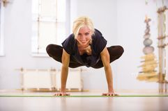 Beautiful sporty fit yogi woman practices yoga asana Padma Bakasana Lotus Crane pose in the fitness room Stock Image