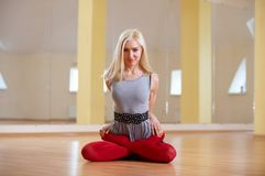 Beautiful sporty fit yogi woman practices yoga asana Padmasana - Lotus pose in the fitness room royalty free stock photo