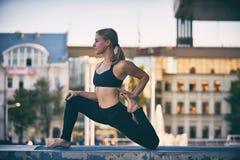 Beautiful young woman practices yoga asana King Pigeon pose rajakapotasana in the city Stock Photo