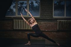 Beautiful sporty fit yogini woman practices yoga asana Utthita Parshvakonasana in the dark hall Stock Photos