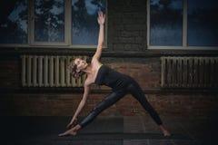 Beautiful sporty fit yogini woman practices yoga asana Utthita Trikonasana - triangle pose in the dark hall Stock Photos