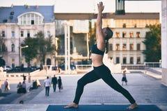 Beautiful young woman practices yoga asana Virabhadrasana 1 - warrior pose 1 in the city royalty free stock photography