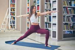 Beautiful sporty fit yogini woman practices yoga asana Virabhadrasana 2 - warrior pose 2 in the library royalty free stock photography
