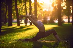 Beautiful young woman practices yoga asana Virabhadrasana 1 - warrior pose 1 in the park at sunset Royalty Free Stock Photography