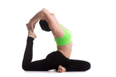 Beautiful sporty girl practices yoga one-legged King Pigeon Pose Stock Image