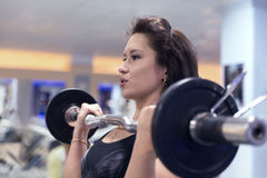 Beautiful sporty girl raises the barbell in the gym. Build muscle arms and chest royalty free stock photos