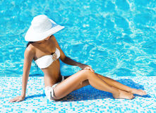 Beautiful and sporty girl relaxing in a pool Stock Photo
