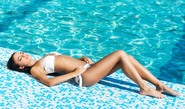 Beautiful and sporty girl relaxing in a pool Stock Photography