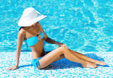 Beautiful and sporty girl relaxing in a swimming pool Royalty Free Stock Images