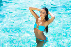 Beautiful and sporty girl relaxing in a swimming pool Stock Photos
