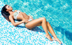 Beautiful and sporty girl relaxing in a swimming pool Royalty Free Stock Photography