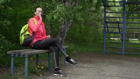 Beautiful sporty girl seated in the bench clean his face with towel, tired blond runner resting after evening jog. Fitness and healthy lifestyle concept stock video