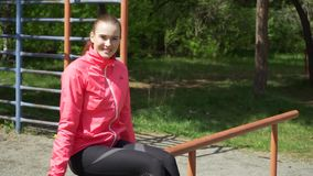 Beautiful sporty girl seated in the bench clean his face with towel, tired blond runner resting after evening jog. Fitness and healthy lifestyle concept stock video footage