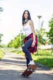 Beautiful girl skateboarder skateboarding in park royalty free stock image