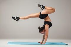 Beautiful sporty girl standing in acrobat pose or yoga asana Royalty Free Stock Image