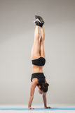 Beautiful sporty girl standing in acrobat pose or yoga asana Royalty Free Stock Images