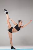 Beautiful sporty girl standing in acrobat pose or yoga asana. On gray background Stock Photo