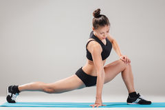 Beautiful sporty girl standing in acrobat pose or yoga asana. On gray background Stock Photography