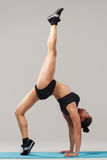 Beautiful sporty girl standing in acrobat pose or yoga asana. On gray background Royalty Free Stock Image