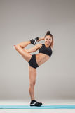Beautiful sporty girl standing in acrobat pose or yoga asana. On gray background Stock Image