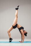 Beautiful sporty girl standing in acrobat pose or yoga asana. On gray background Royalty Free Stock Photography