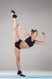 Beautiful sporty girl standing in acrobat pose or yoga asana. On gray background Stock Images