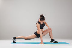 Beautiful sporty girl standing in acrobat pose or yoga asana. On gray background Stock Photos