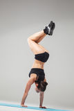 Beautiful sporty girl standing in acrobat pose or yoga asana. On gray background Royalty Free Stock Photo