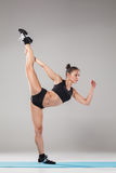 Beautiful sporty girl standing in acrobat pose or yoga asana. On gray background Royalty Free Stock Images
