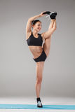 Beautiful sporty girl standing in acrobat pose or yoga asana Royalty Free Stock Photo