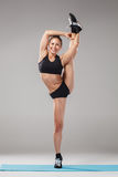 Beautiful sporty girl standing in acrobat pose or yoga asana Stock Photo