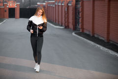 Beautiful sporty girl using device walking in the street stock image