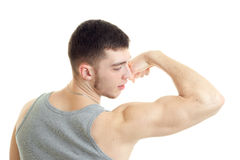 Beautiful sporty guy stands with his back to the camera and strain on the arm muscles closeup Stock Images
