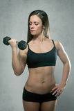 Beautiful sporty muscular woman with dumbbell Royalty Free Stock Image