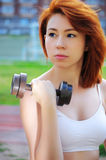 Beautiful sporty red-haired girl goes in for sports in the street with a metal dumbbell Royalty Free Stock Photography